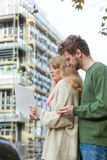 Couple with blueprint project keys on construction site. Real estate and family concept - young couple on front of new big modern house construction site with Royalty Free Stock Image