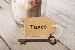 Real estate finance concept - money glass with Taxes word. And vintage key royalty free stock photo