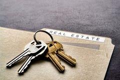 Real Estate Folder and Set of House Keys on Desk royalty free stock image