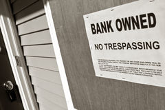 Real Estate Foreclosure Bank Owned Sign on House royalty free stock image