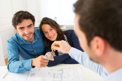 Real estate handing over keys to couple. View of a Real estate handing over keys to couple Stock Image