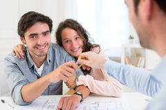 Real estate handing over keys to couple Royalty Free Stock Photos