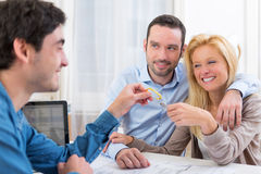 Real estate handing over keys to couple. View of a Real estate handing over keys to couple Royalty Free Stock Photos