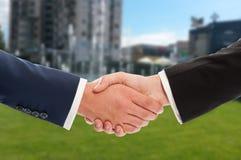 Real estate handshake over building and property for sale backgr Stock Image