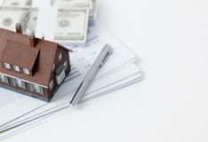 Real estate and home loan. Model house, calculator, cash money and paperwork on a desk: real estate, home loan and investments concept royalty free stock images
