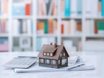 Real estate and home loan. Model house, calculator, cash money and paperwork on a desk: real estate, home loan and investments concept stock photo