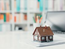 Real estate and home loan. Model house and paperwork on a desktop: real estate, investments and home loan concept stock photos