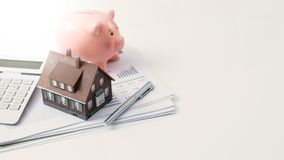 Real estate, home loan and mortgages. Model house, piggy bank, calculator and financial report on a desk: real estate, investments and home loan concept stock images