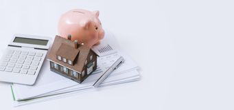 Real estate, home loan and mortgages. Model house, piggy bank, calculator and financial report on a desk: real estate, investments and home loan concept Royalty Free Stock Photos