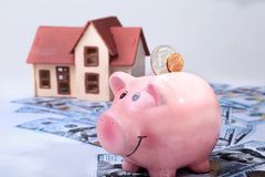 Real estate or home saving. piggy bank with coins on blur background money and house. Real estate or home saving. piggy bank with coins on blur background money royalty free stock images