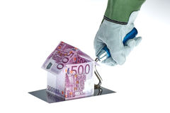 Real estate. House construction cost symbolized by money in house shape on workers trowel stock photography