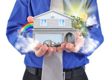 Real Estate House in Hands. A man is holding a house in his hands with a rainbow and clouds. There is a key for the home ownership Stock Photos