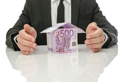 Real estate and insurance crisis solution. Male hands around house made of Euro money. Concept of real estate and insurance crisis solution Stock Photography