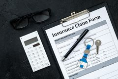 Real estate insurance. Insurance claim form near house keychain on black background top view royalty free stock images