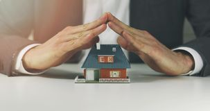 Real estate insurance and security concept. Hands shielding house scale model stock video footage