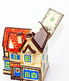 Real Estate Investment. Million dollar bill  coming out of a ceramic house.  A real estate investment concept Stock Photos