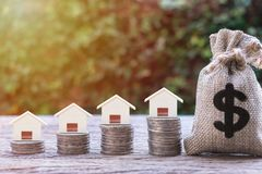 Real estate investment, home loan, mortgage, housing concept. House model on stack of coins and US dollar money bag, Depicts saving and money management for royalty free stock images