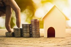 Real estate investment, home loan, savings to buy home concepts. House wooden model , Fingers climb on coins. depicts a funding or growing money for real stock image