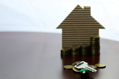 Real estate keys paper house. Real estate keys and paper house on a table Stock Photo