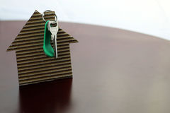 Real estate keys paper house. Real estate keys and paper house on a table Stock Image