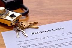 Real Estate Listing Document on Realtor Desk. Real estate broker listing home seller document on Realtor desk with house keys and safety showing lock box on Stock Photo