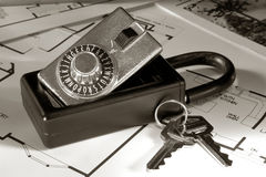 Real Estate Lock Box and Keys on House Floor Plans. Real estate Realtor combination lock box with set of house keys over home builder construction layout floor stock photos