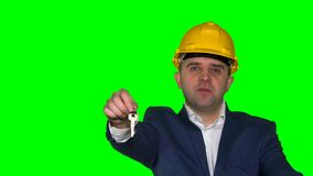 Real estate male customer holding key of new apartment in realtor office. Green even chroma key background. Static closeup shot. 4K UHD stock video footage