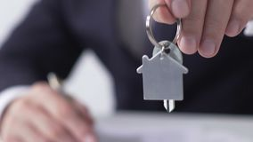 Real estate manager giving key from dream house to buyer, signing rent agreement. Stock footage stock video footage