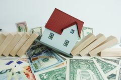 Real estate market collapse concept with model house crashed by domino pieces stock photo