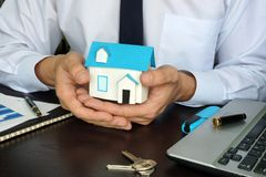 Real estate marketing. Agent holding model of house Stock Images