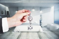 Real estate, mortgage concept. Hand holding key in modern bedroom interior. Real estate, mortgage concept. 3D Rendering Stock Image