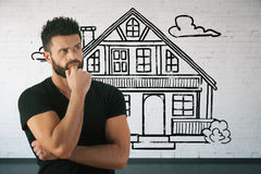 Real estate and mortgage concept. Thoughtful bearded young man in brick interior with drawn house. Real estate and mortgage concept. 3D Rendering royalty free stock images