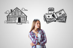 Real estate, mortgage and housing. Attractive caucasian girl on grey background with house and money sketch. Real estate, mortgage and housing concept royalty free stock images