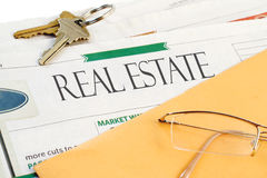 Real estate news. Real estate section of the newspaper with yellow envelope, eyeglasses and keys Royalty Free Stock Image