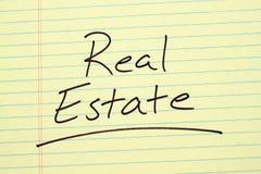 Real Estate på ett gult lagligt block Arkivbild