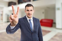 Real estate person showing peace victory gesture on building lo royalty free stock image