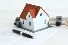 Real estate prices or crisis concept with house in a clamp tool Stock Photo