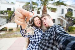 Real estate and property concept - Happy couple holding keys to new home and house miniature.  royalty free stock photo