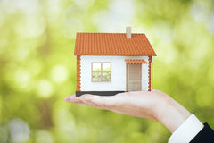 Real estate, property and mortgage concept. Hand holding small house model on blurry green background. Real estate, property and mortgage concept. 3D Rendering Royalty Free Stock Photos
