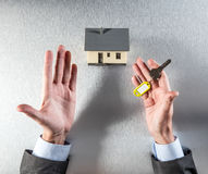 Real estate question about renting, selling or buying your house. With the symbol of a home key in tensed businessman hands for investment stress, top view Royalty Free Stock Images