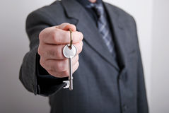 Real estate rep. A real estate agent holds out the front door key of a new home to a lucky buyer Royalty Free Stock Images