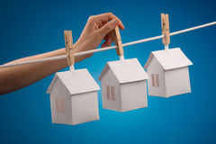 Paper houses on line. Paper houses hanging from drying line on blue background Stock Images