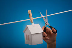 Real estate for sale. Paper house with clothespin, hanging from rope on blue background. Selective focus Royalty Free Stock Image