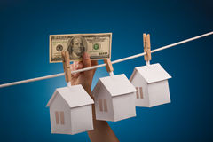 Real estate for sale. Paper house with clothespin, hanging from rope on blue background. Selective focus Stock Photos