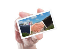 Real estate sale handshake on paper card. Hold by hand isolated on white background Stock Image