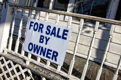 Real Estate For Sale by Owner Sign on Old House. For sale by owner real estate sign hanging on the front porch railing of a poorly maintained old house stock photography