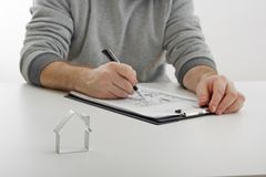 Real estate. Sale of real estate, signing a contract, signing. Businessman signs contract behind home architectural model Royalty Free Stock Photo