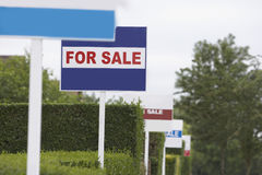 Real estate for sale signs in a row by hedges Stock Image