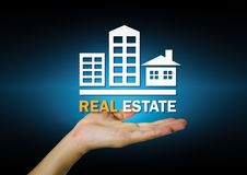 Real estate. Sign on hand with dark background Stock Image