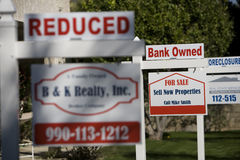 Real Estate Signs at Foreclosed Property. Closeup of real estate signs at foreclosed property Royalty Free Stock Photos